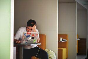 Pria stress di depan laptop. multasking bisa menyebabkan stress
