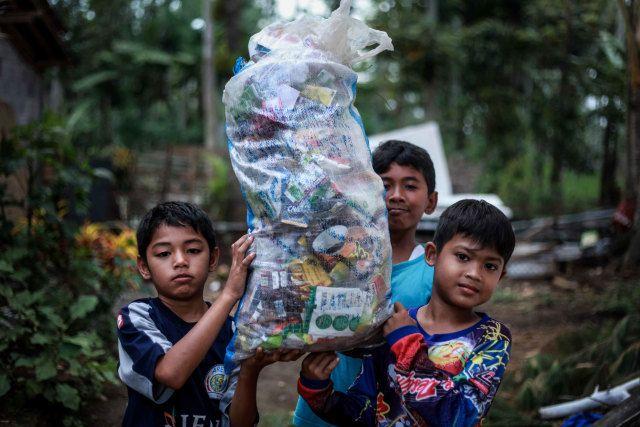 anak-anak membawa sampah. Menengok Gubuk Baca Lereng Busu: Kala Sekolah Cukup Dibayar dengan Sampah