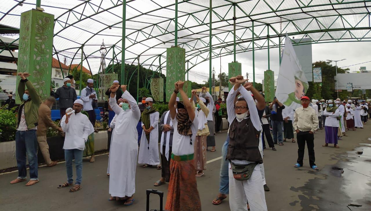 Massa aksi Muslim Malang Bersatu mengepalkan tangan terborgol sebagai aksi solidaritas menuntut pembebasan Habib Rizieq, Jumat (18/12). (Foto: Azm/Tugu Malang/Tugu Jatim)