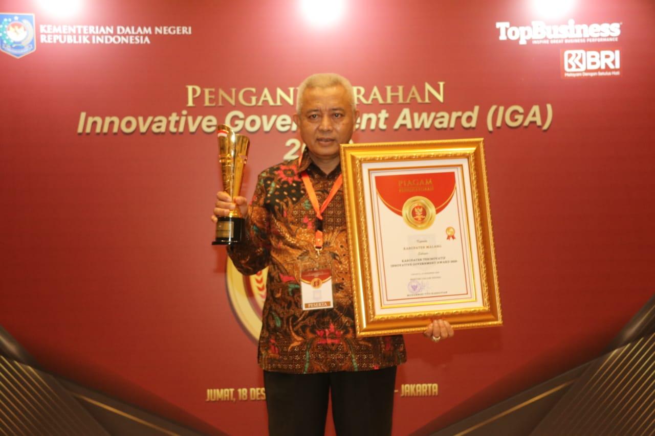 Bupati Malang, Sanusi memaerkan penghargaan dari Mendagri, Tito Karnavian. (Foto: Humas Pemkab Malang)