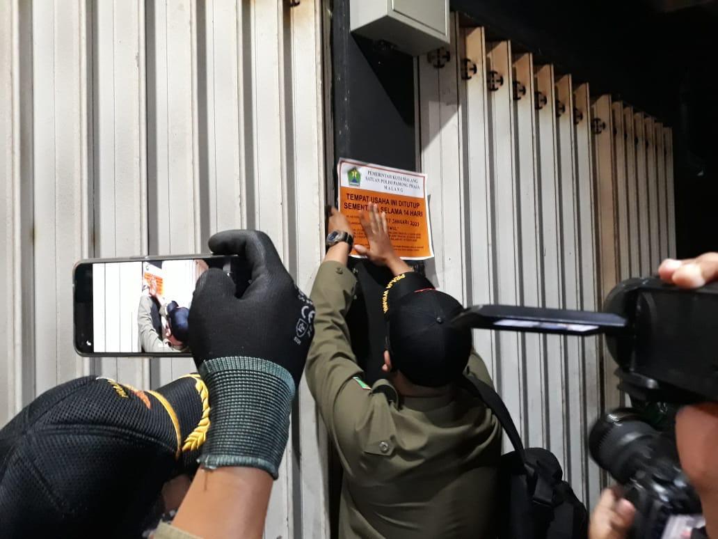 Petugas Satpol PP Kota Malang tengah melakukan penyegelan terhadap salah satu kafe akibat bandel tetap beroperasional di luar jam ketentuan PPKM, Jumat (15/01/2021). (Foto : Azmy)