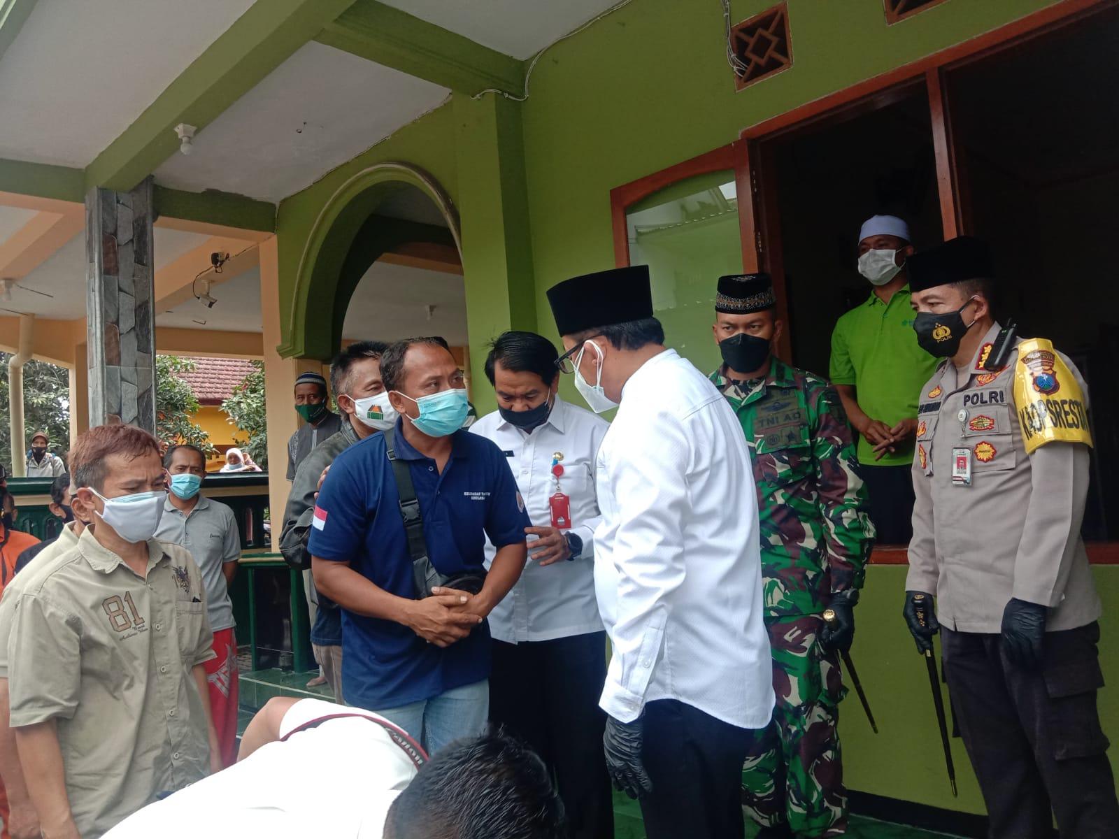 Wali Kota Malang Sutiaji sedang berkoordinasi dengan keluarga Roland Sumarna, korban plengsengan ambrol di Kota Malang, saat persiapan pemakaman jenazah. (Foto: Feni Yusnia/Tugu Malang)