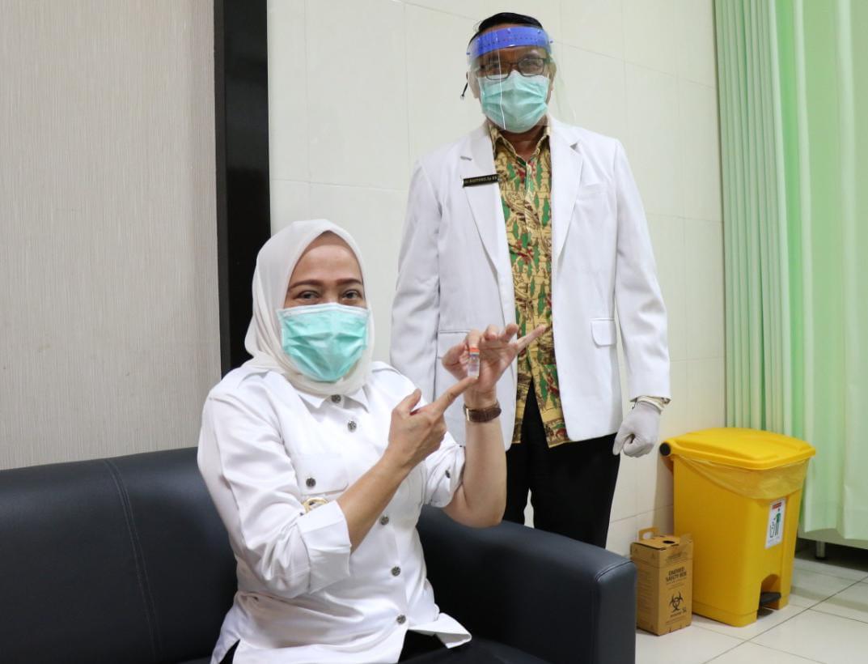 Bupati Bojonegoro Anna Muawanah agar tak terpapar Covid-19 mengikuti kegiatan vaksinasi. Dia juga menunjukkan vaksin sinovac yang akan disuntikkan. (Foto: Mila Arinda/Tugu Jatim)