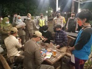 Petugas memeriksa identitas pengunjung kafe pada PPKM tahap kedua. (Foto: Humas Polres Tuban/Tugu Jatim)