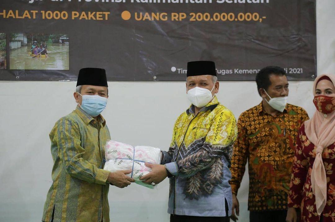 Sekjen Kemenag RI Nizar Ali (kanan) menyerahkan bantuan untuk warga terdampak banjir kepada Kakanwil Kemenag Kalimantan Selatan Noor Fahmi (kiri). (Foto:Humas Kemenag RI/Tugu Jatim)
