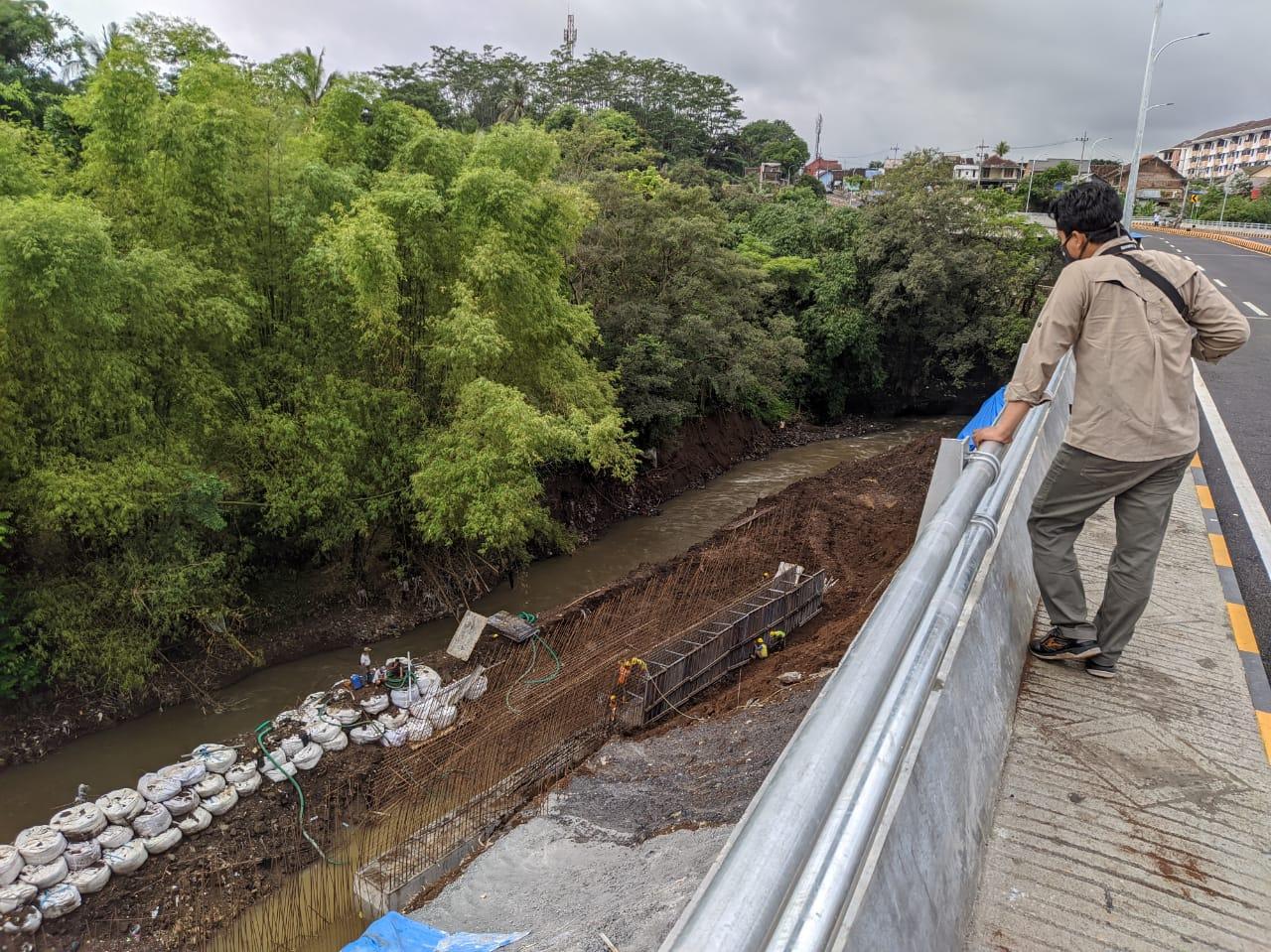 Pengerjaan bagian plengsengan di bawah Jembatan Kedungkandang masih dalam tahap pengerjaan pasca ambrol beberapa waktu lalu. (Foto: Azmy/Tugu Malang/Tugu Jatim)