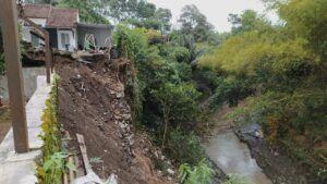 Lokasi tanah plengsengan yang longsor di bibir Sungai Bango setinggi 15 meter. (Foto: Azmy/Tugu Jatim)