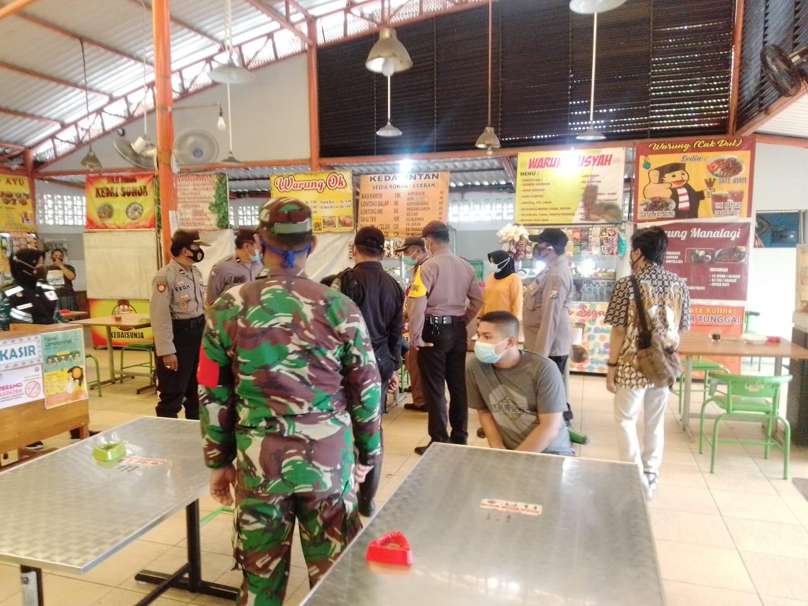 Tim Gabungan dari tiga pilar meliputi Kecamatan Wiyung, Polsek Wiyung, Koramil Wiyung, Satpol-PP Wiyung dan jajaran melakukan inspeksi mendadak (sidak) operasi yustisi di Sentra Kuliner Jajartunggal, Surabaya, Jumat (05/02/2021), pukul 10.00 WIB. (Foto: Rangga Aji/Tugu Jatim)