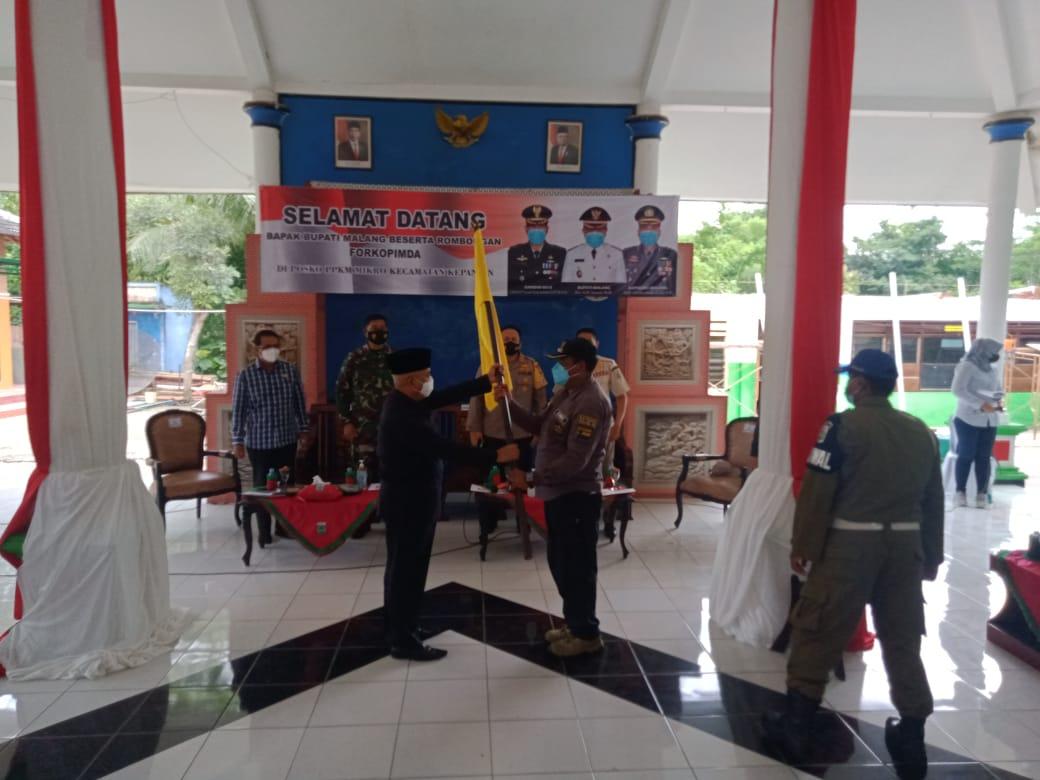 Bupati Malang Muhammad Sanusi menyerahan bendera zonasi Covid-19 kepada Camat Kepanjen. (Foto: Rap/Tugu Jatim)