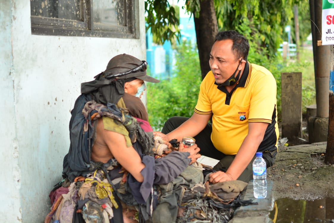 Aipda Purnomo membujuk ODGJ di Lamongan agar mau pakaiannya yang terbuat dari puluhan potongan kain itu diganti. (Foto: Dok Aipda Purnomo/Mila Arinda/Tugu Jatim)