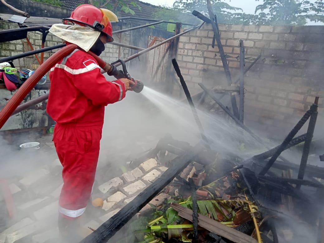 Petugas BPBD Tuban dibantu warga, TNI, dan Polri untuk memadamkan kebakaran yang menghanguskan rumah warga akibat korsleting listrik. (Foto: Humas BPBD Tuban/Tugu Jatim)