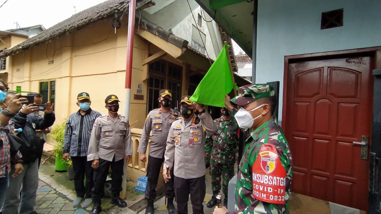 Kapolresta Malang Kota Kombes Pol Leonardus Simarmata menunjukkan bendera zonasi hijau di RW 1, Kelurahan Sukoharjo, Klojen, Kota Malang, Sabtu (13/02/2021). (Foto: Azmy/Tugu Jatim)