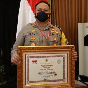 Kapolres Malang AKBP Hendri Umar saat menerima penghargaan. (Foto: Humas Polres Malang/Tugu Jatim)