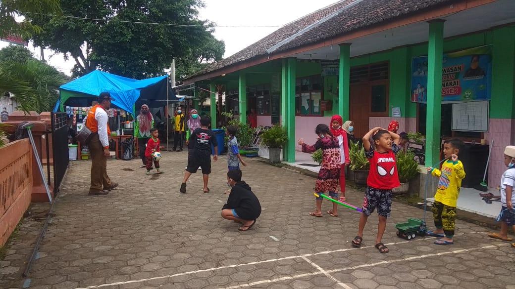 Anak-anak yang mengungsi karena bencana longsor sedang bermain di halaman SDN 3 Ngetos, Nganjuk. (Foto: Noe/Tugu Jatim)