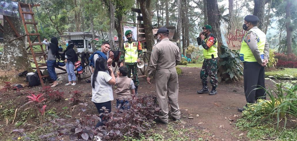 Babinsa Puspo, Pasuruan, patroli protokol kesehatan kepada pengunjung Tempat Wisata Red Flower. (Foto: Dok/Tugu Jatim)
