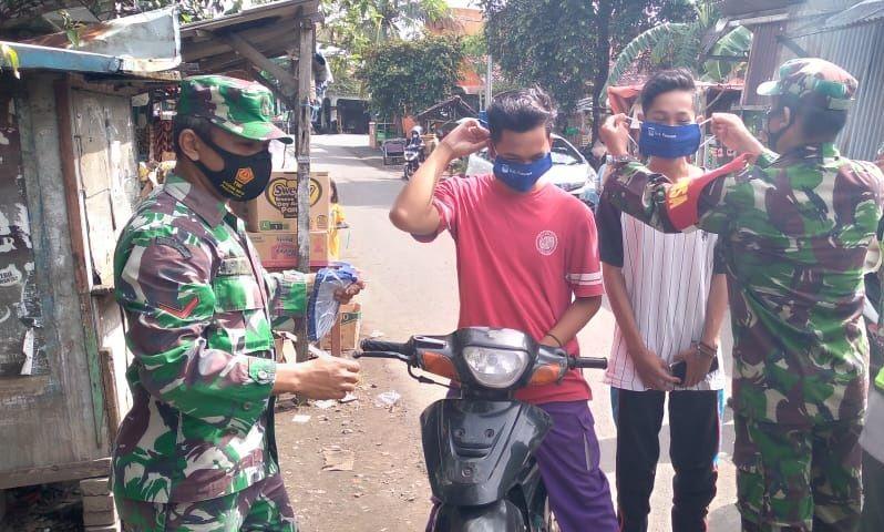 Anggota TNI dari Koramil Kraton Kodim 0819 Pasuruan bagikan masker ke masyrakat. (Foto: Dokumen)