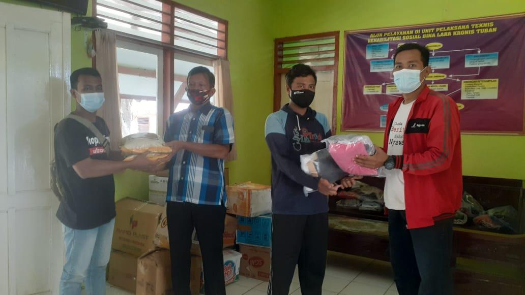 Koordinator Kegiatan Baksos Forum Biker Tuban Suwandi (berjaket merah) menyerahkan bantuan baju layak pakai dan sembako secara simbolis kepada Perwakilan UPT Rehabilitasi Eks Penderita Kusta. (Foto: Istimewa/Tugu Jatim)