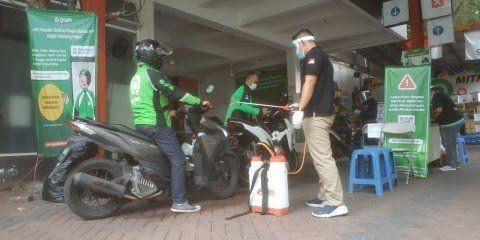 Driver ojol saat melakukan sterilisasi kendaraan di Posko J3K Kantor Gojek Malang. (Foto: Azmy/Tugu Malang/Tugu Jatim)