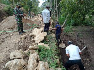 Anggota TNI dari Kodim 0801/Pacitan Jawa Timur yang turun membantu membangun jalan desa di Desa Widoro, Kecamatan Donorojo, Kabupaten Pacitan, dalam program TMMD ke-110, Rabu (10/2/2021). (Foto: Dokumen/Kodim 0801 Pacitan) tugu jatim
