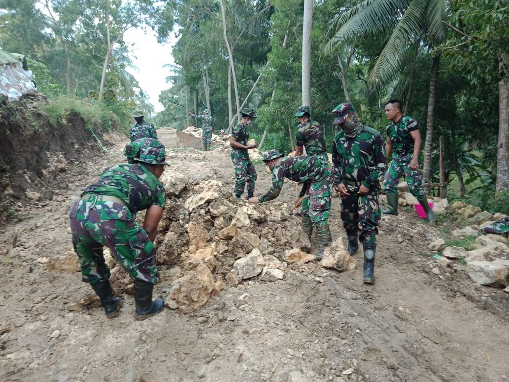 Anggota TNI dari Kodim 0801/Pacitan Jawa Timur yang turun membantu membangun jalan desa di Desa Widoro, Kecamatan Donorojo, Kabupaten Pacitan, Rabu (10/2/2021). (Foto: Dokumen/Kodim 0801 Pacitan) tugu jatim