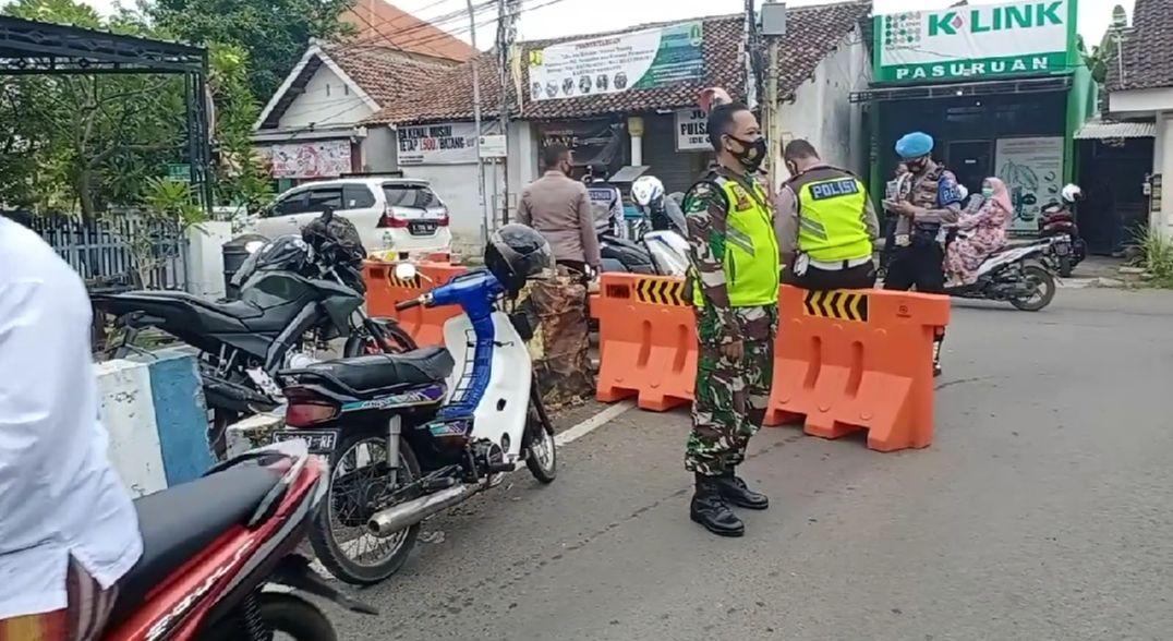 Koramil dan Polsek Gadingrejo melakukan penutupan pasar tumpah di Jalan Raden fatah (Karya Bakti) Kelurahan Gentong, Kecamatan Gadingrejo, Kota Pasuruan, Minggu(14/02/21)