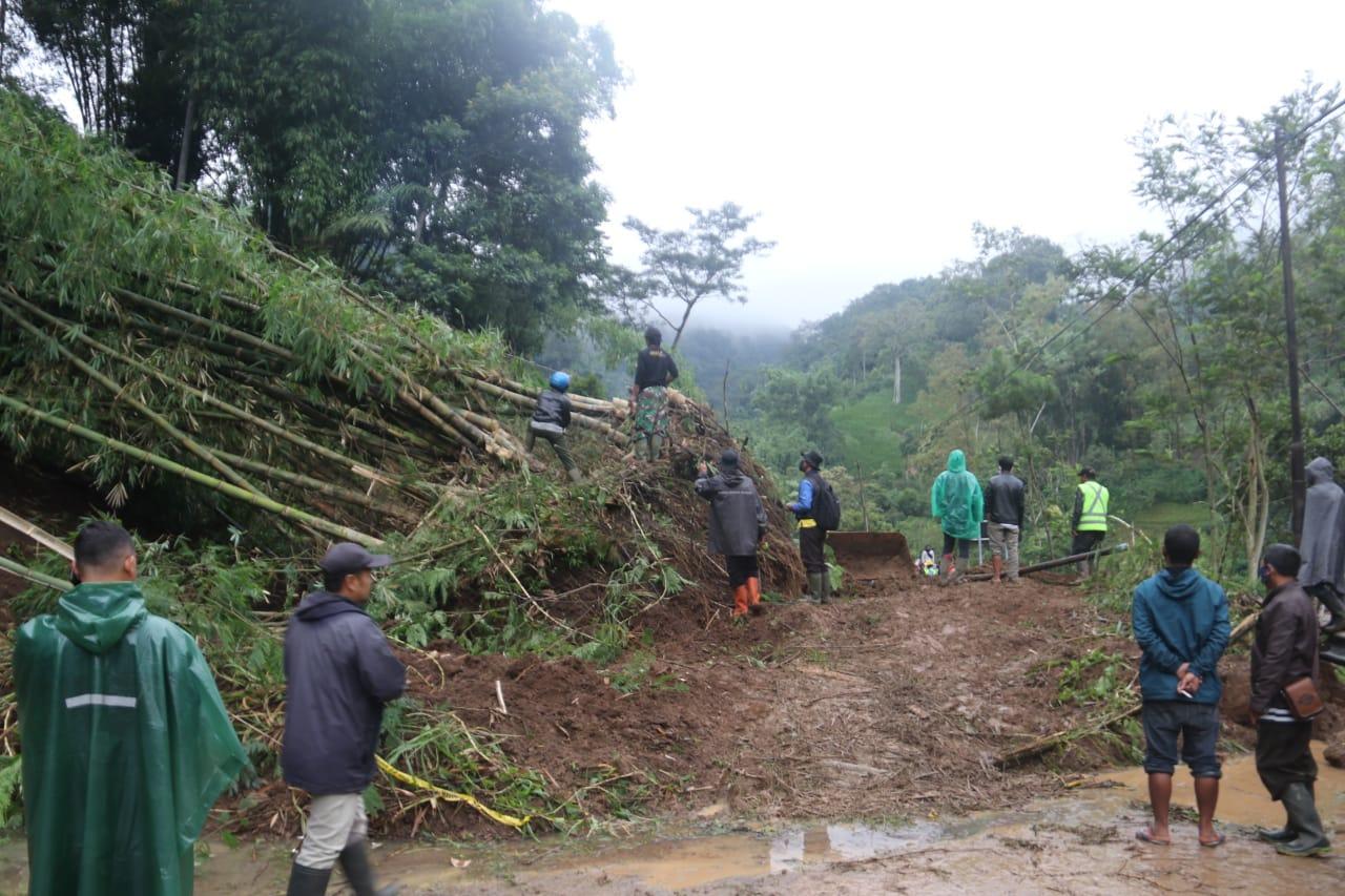 Para petugas berusaha memberishkan material tanah longsor yang menutup akses jalan dari Kota Malang menuju Kediri. (Foto: Dokumen/Tugu Malang)