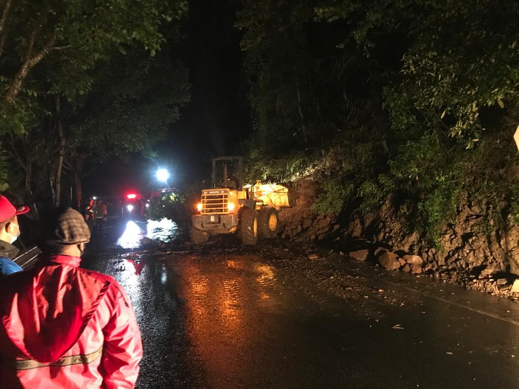 Petugas membersihkan material longsor di jalur kawasan Payung Kota Batu dengan alat berat, Sabtu (27/2/2021). (Foto : Pusdalops BPBD Kota Batu) tanah longsor, jalur malang-kediri, tugu jatim