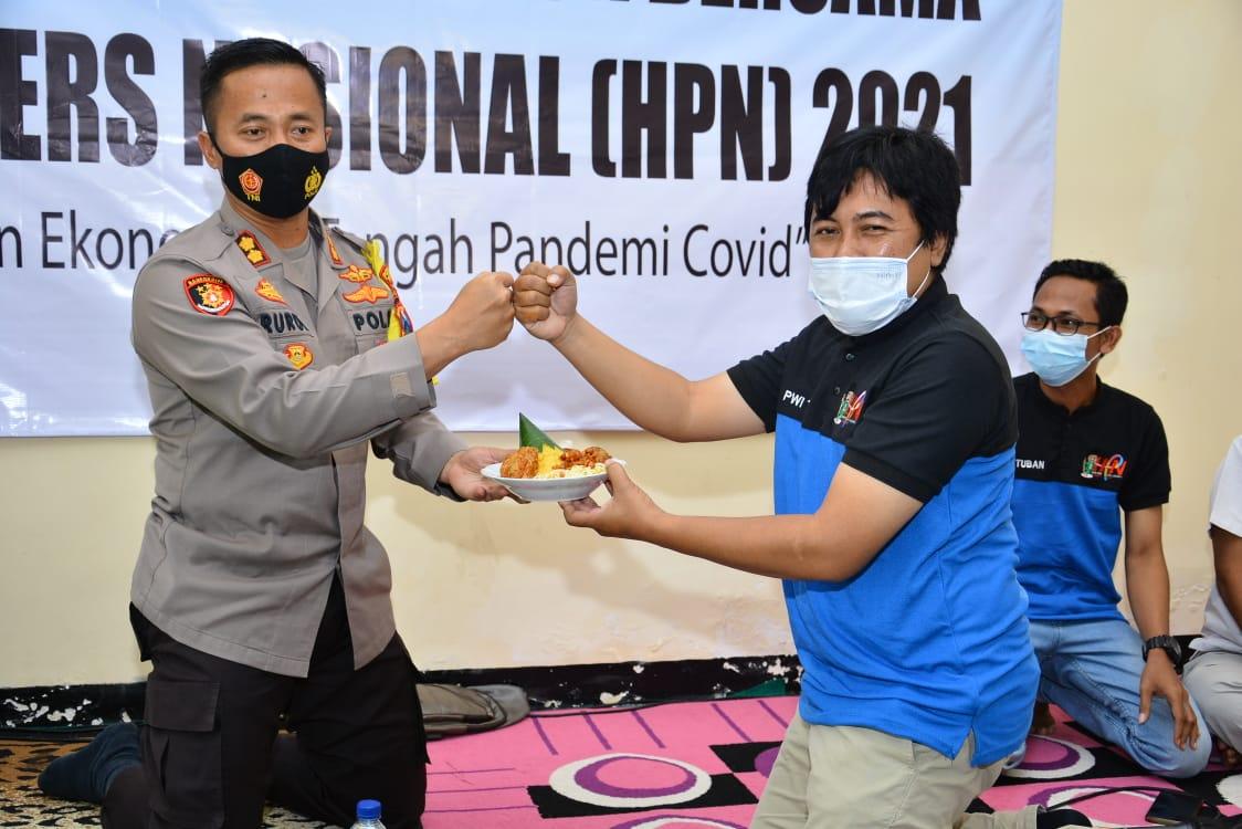 Ketua PWI Tuban, Pipiet Wibawanto saat memotong tumpeng dan diserahkan ke Kapolres Tuban, AKBP Ruruh Wicaksono. (Foto: Moch Abdurrochim/Tugu Jatim)
