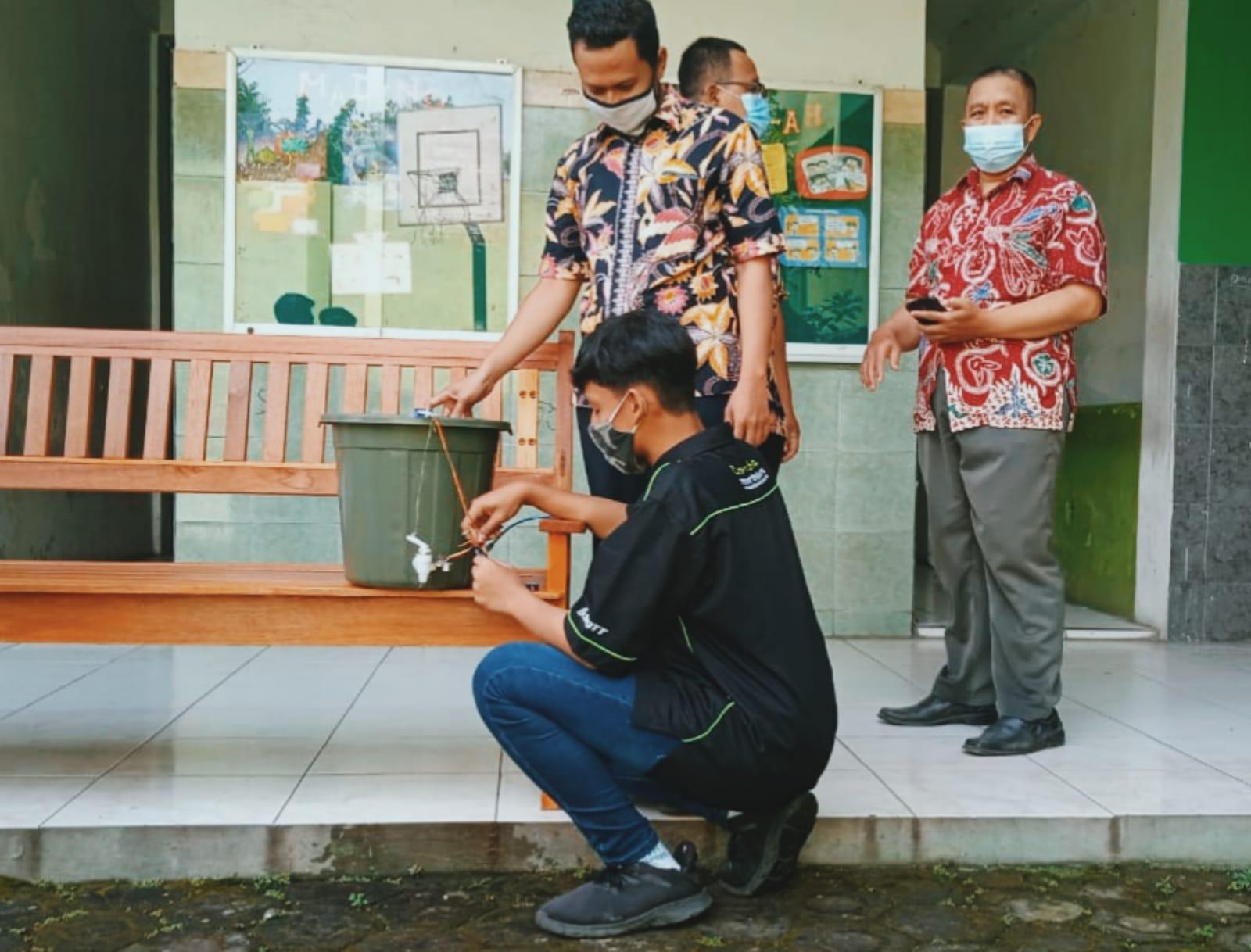 Ibrahim Khalilullah (siswa yang memakai baju hitam) dan Khoirul Muhlisin (siswa yang memakai baju motif kotak-kotak) sedang mencoba alat cuci tangan sensor. (Rangga Aji/Tugu Jatim) SMK YPM 11 Wonoayu, alat cuci tangan otomatis sensor elektronik