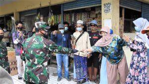 Bagi-bagi masker oleh anggota Kodim 0819 Pasuruan di Pasar Kebon Agung dan Pasar Warungdowo, Sabtu (6/2/2021). (Foto: Dokumen) tugu jatim