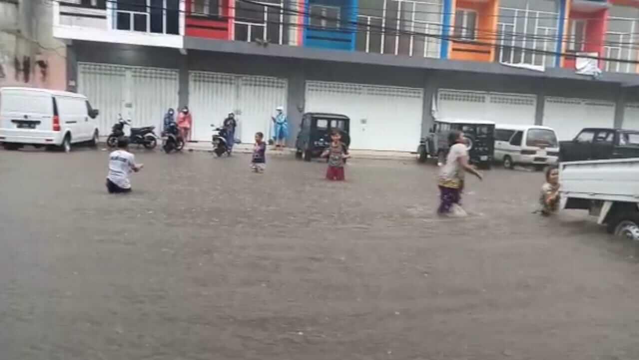 Anak-anak memanfaatkan banjir di kawasan Jalan Kedawung, Kota Malang, dengan berenang secara gratis Senin (22/03/2021). (Foto: Azmy/Tugu Jatim)