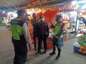 Petugas memakaikan masker kepada warga yang langgar prokes. (Foto:Dok/Tugu Jatim)