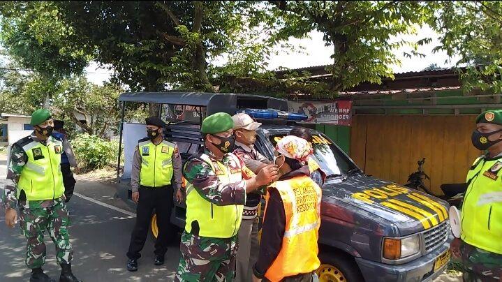 Babinsa Pasuruan melaksanakan operasi masker kepada warga. (Foto:Dok/Tugu Jatim)