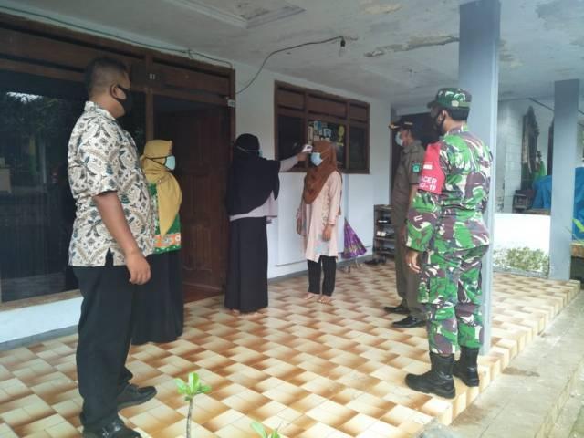 Babinsa Pasuruan mendampingi petugas Puskesmas Lumbang untuk melakukan tracing. (Foto:Dok/Tugu Jatim)