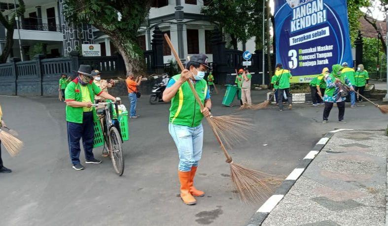 Mantan Sekda Kota Malang Wasto saat menyapu jalanan bersama Kader Lingkungan pada Senin (01/03/2021). (Foto: Azmy/Tugu Jatim)