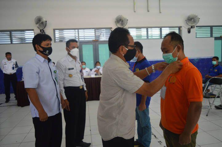 Kepala Lapas Kelas II B Tuban Siswarno didampingi perwakilan BLK Tuban saat menyematkan ID Card ke perwakilan peserta pelatihan. (Foto: Rochim/Tugu Jatim)