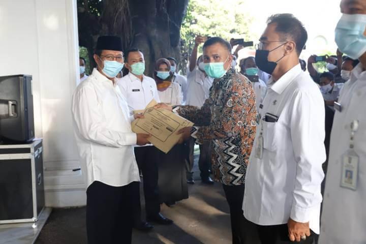 Bupati Tuban, Fathul Huda saat menyerahkan naskah ujian perangkat desa tahun 2021 kepada Panitia Pelaksana tingkat kecamatan, Rabu (24/3/2021). (Foto: Humas Pemkab Tuban)