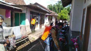 Anggota CCF menyemprotkan disinfektan ke rumah warga. (Foto: Dok/Tugu Jatim)