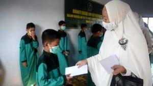Ketua Persit KCK Cab XXXIII Pasuruan Ibu Deti Burhan memberikan santunan kepada salah satu anak yatim. (Foto: Dok/Tugu Jatim)