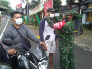 Petugas memakaikan masker kepada warga. (Foto:Dok/Tugu Jatim)