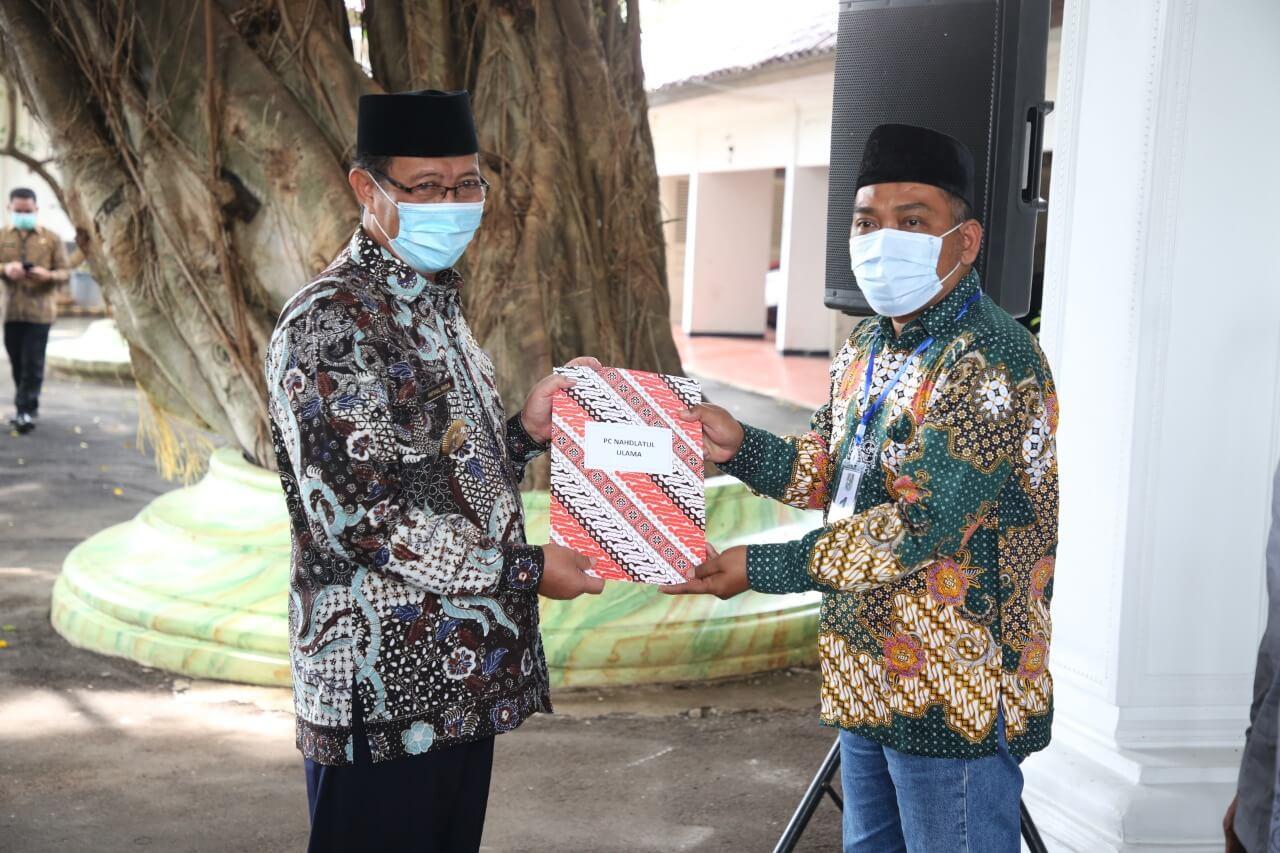 Bupati Tuban, H. Fathul Huda menyerahkan dana hibah kepada perwakilan dari Ormas NU Tuban, dan beberapa Ponpes serta TPQ lainnya. (Foto: Humas Pemkab Tuban) tugu jatim