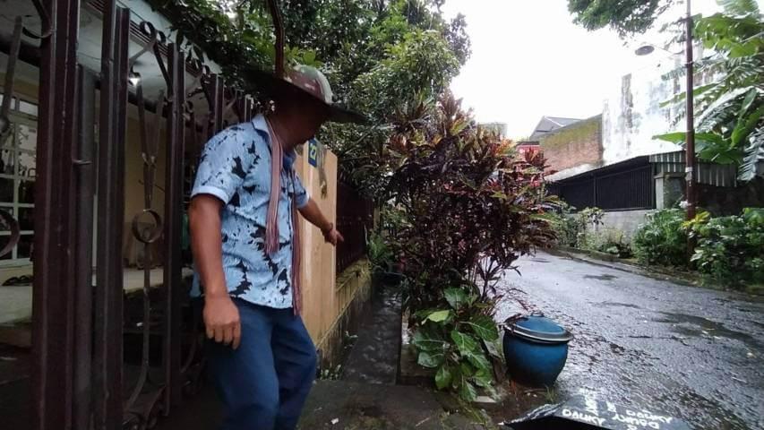 Warga menunjukkan lokasi temuan hewan diduga buaya yang sedang melintas di parit perumahan warga. (Foto : Azmy/Tugu Malang/Tugu Jatim)