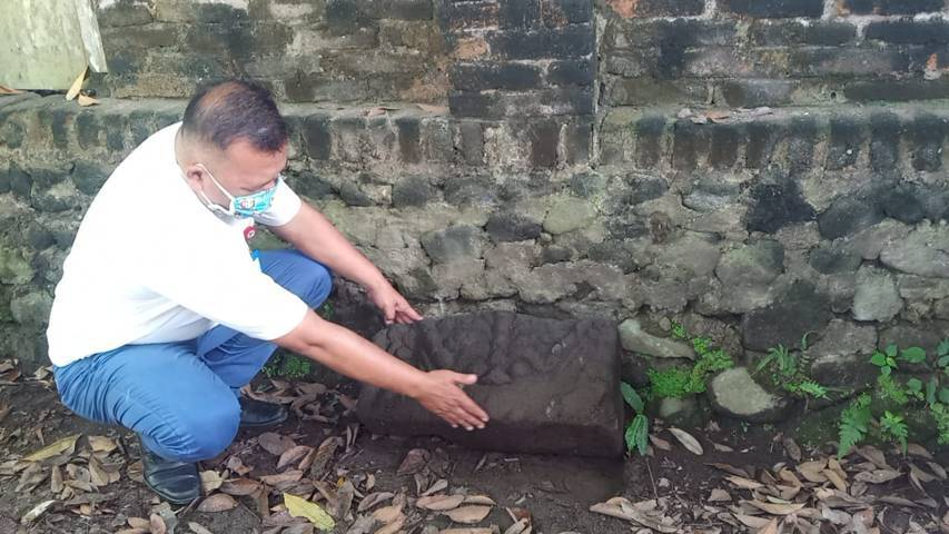 Kabid Sejarah dan Purbakala Disparbud Kabupaten Kediri Yuli Marwanto yang memegang cagar budaya berupa kepala kala. (Foto: Noe/Tugu Jatim)