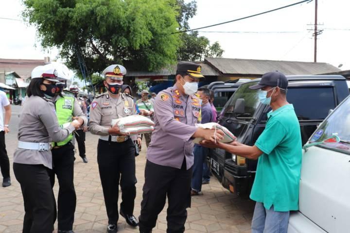 Kapolres Batu AKBP Catur C. Wibowo memberikan bantuan sembako kepada masyarakat di pasar. (Foto: Sholeh/Tugu Jatim)