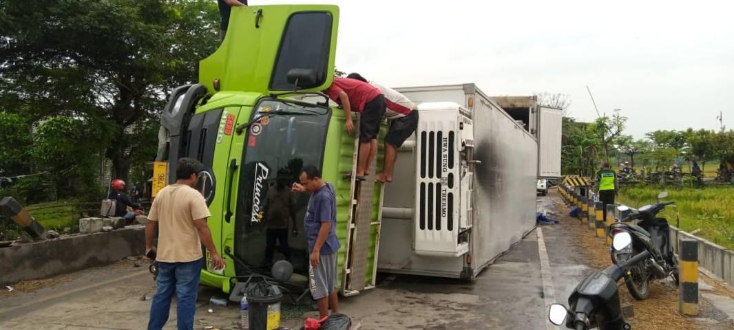 Kondisi truk yang terguling di Jalur Pantura Tuban, tepatnya di Jembatan Kepet, tepatnya jalan Tuban-Surabaya, Dusun Kepet, Desa Tunah, Kecamatan Semanding, Kabupaten Tuban. (Foto: Rochim/Tugu Jatim)