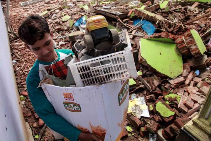 Warga tengah melakukan proses evakuasi dan menyelamatkan barang-barang mereka yang tersisa dari timbunan puing-puing. (Foto: Bayu Eka Novanta/Tugu Malang/Tugu Jatim)