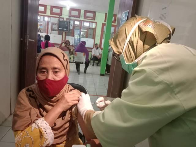 Salah satu lansia perempuan yang menjalani vaksinasi di Puskesmas Batu, Kota Batu. (Foto: Sholeh/Tugu Jatim)