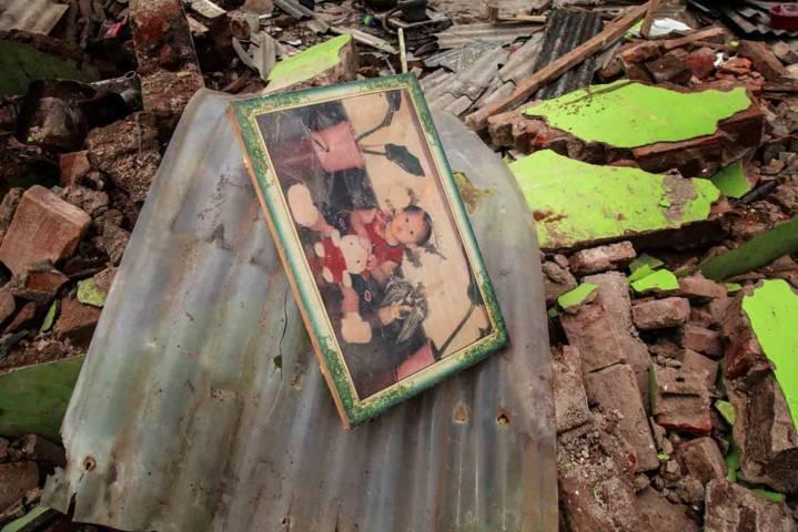 Foto keluarga di antara reruntuhan puing-puing rumah yang telah rata dengan tanah. (Foto: Bayu Eka Novanta/Tugu Malang/Tugu Jatim)