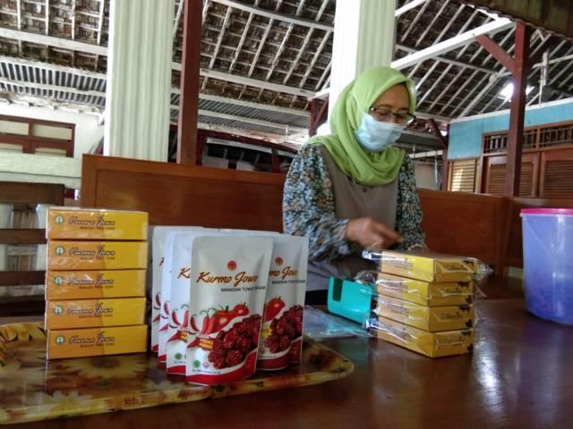 Endah sedang mengemas Kurmo Jowo, manisan buah tomat di Desa Mojodeso, Kecamatan Kapas, Kabupaten Bojonegoro. (Foto: Mila Arinda/Tugu Jatim)