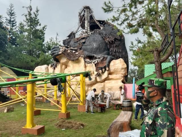 Petugas mengevakuasi reruntuhan patung gorila dengan pengamanan aparat TNI. (Foto: Sholeh/Tugu Jatim)